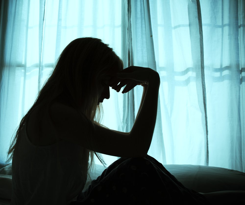 Silhouette of woman sitting in bed by window