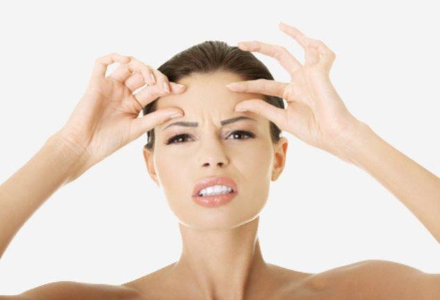 Frau untersucht ihre Falten auf der Stirn