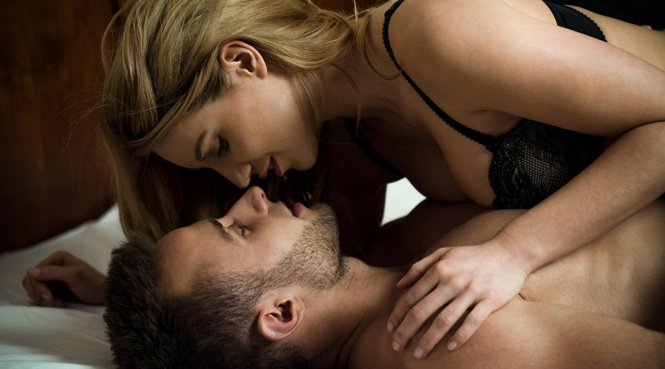 Woman seducing man lying on him in sexy lingerie