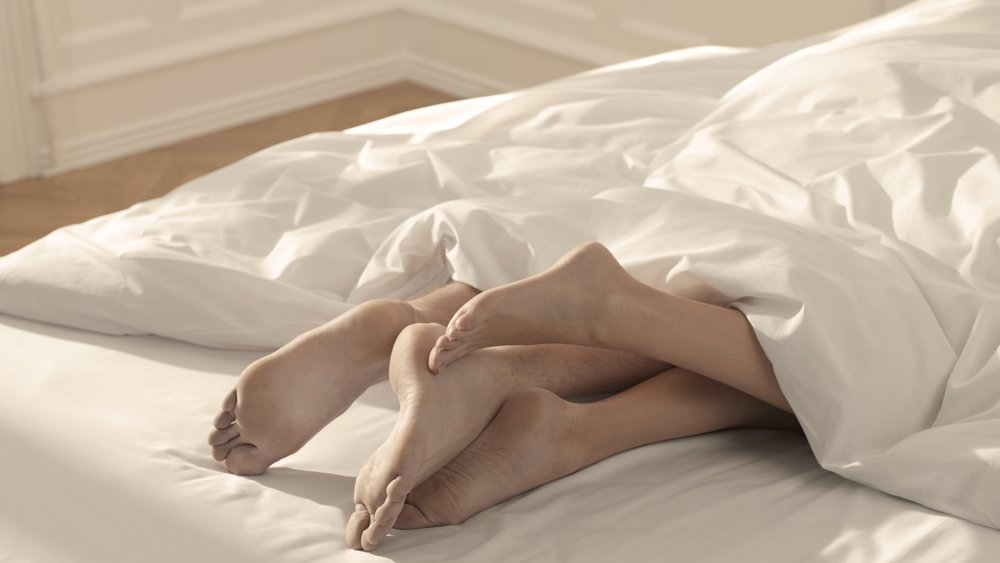 A couple's feet poke out of the bottom of a duvet in bed.