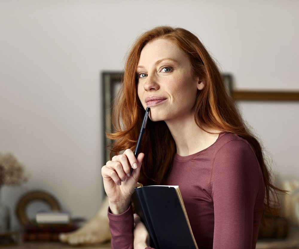 Portrait of smiling woman with book and pen. Young female is wearing casuals. She is at home.