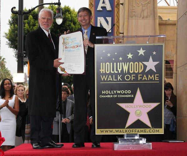The Mentalist-Darsteller Malcolm McDowell erhält eine Urkunde.