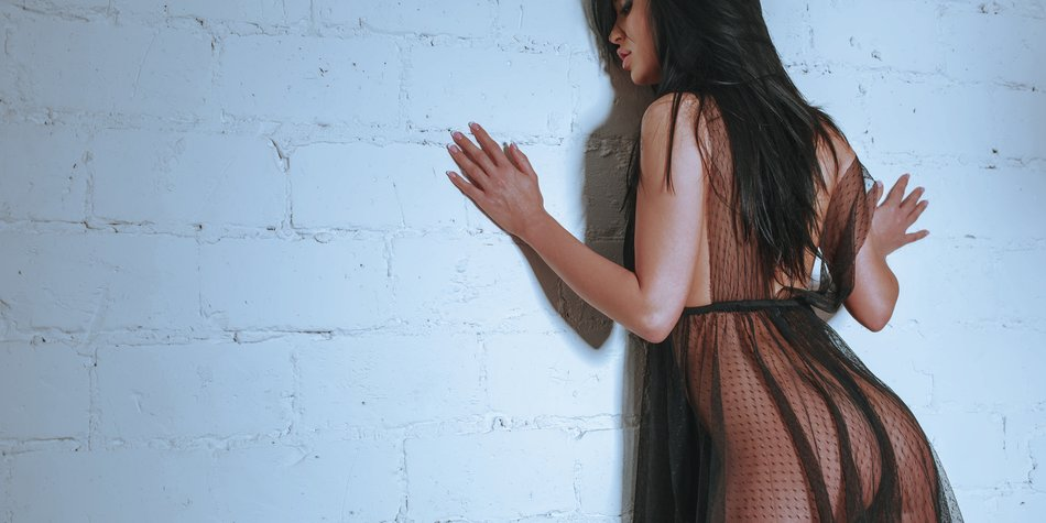 girl leaning against a wall in a sexy transparent dress