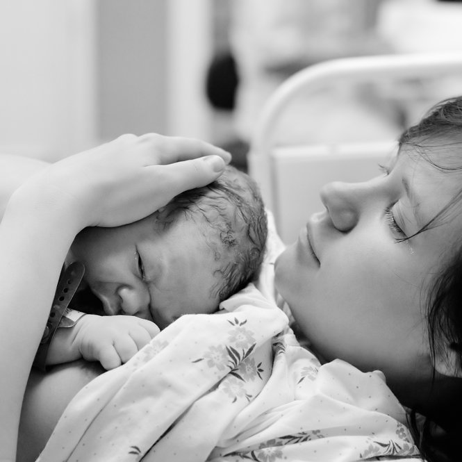 Black and white shot of young woman with newborn baby right after delivery