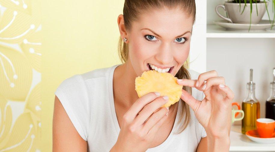 Frau isst Ananas
