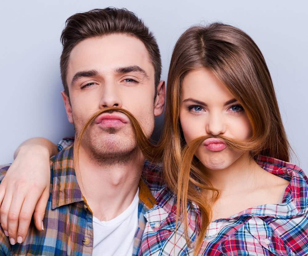 Beautiful young loving couple making fake moustache from hair while standing against grey background