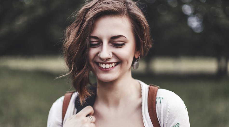 Portrait of a beautiful smiling girl outdoors. Attractive young girl laughs and looks shyly down