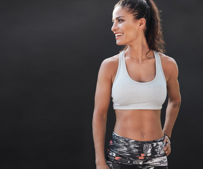 Happy young woman in sports clothing smiling. Muscular fitness model on black background looking away at copy space.