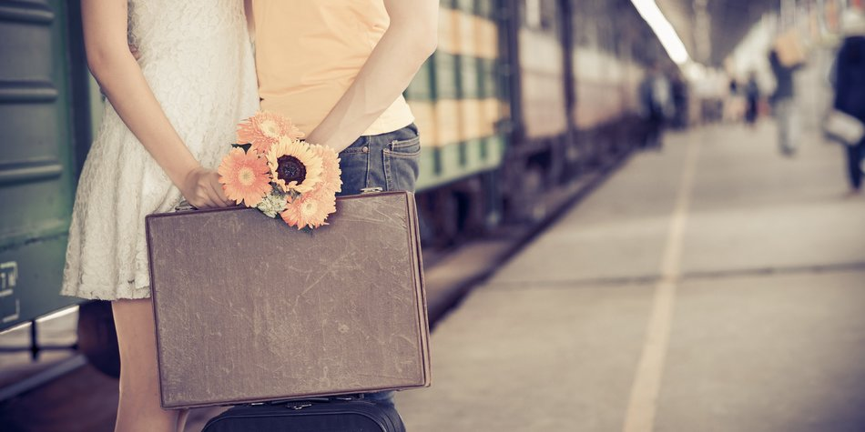 Cropped image of girl giving farewell kiss to her boyfriend at the railway station