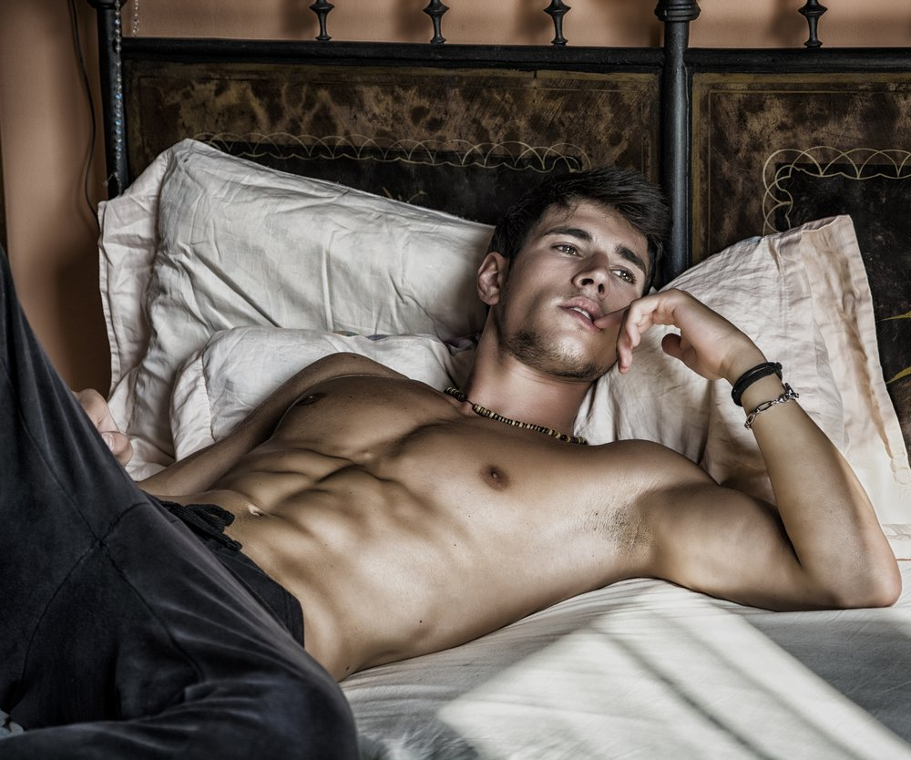 Shirtless sexy male model lying alone on his bed in his bedroom, looking away with a seductive attitude