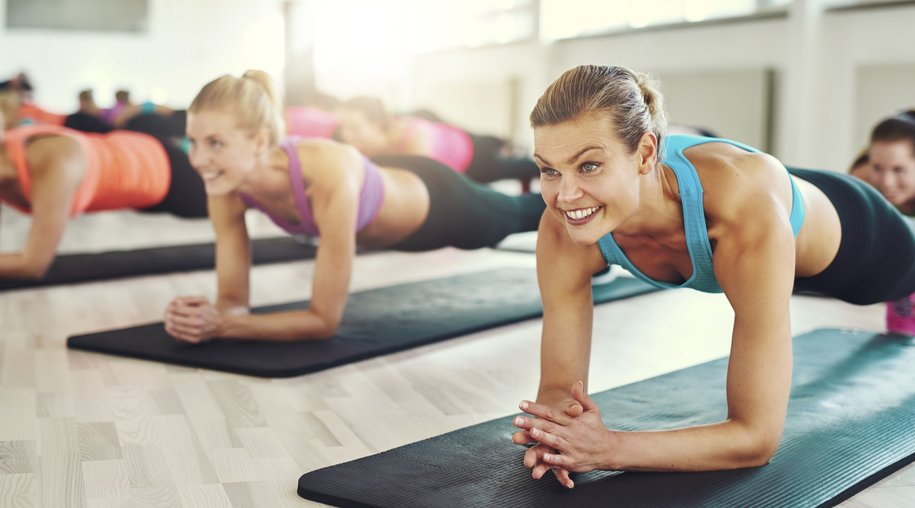 Group of Healthy Young Women Doing Planking Exercise on their Yoga Mats Inside at the Fitness Studio.