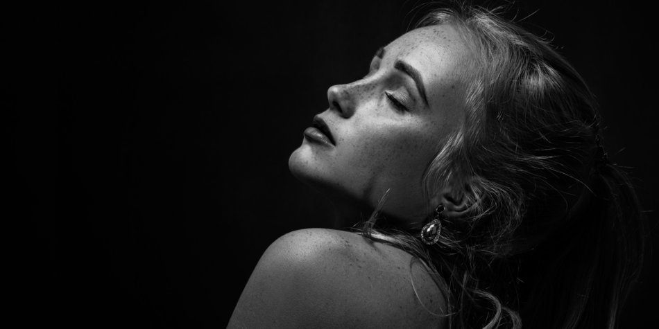 sensual aroused woman with freckles in dark, monochrome
