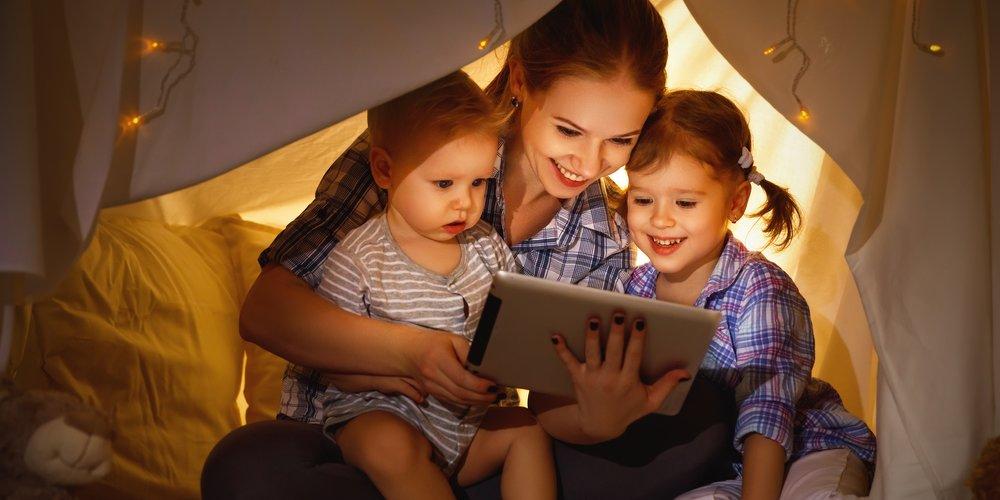 Mutter sitzt mit ihren Kindern in einem Zelt