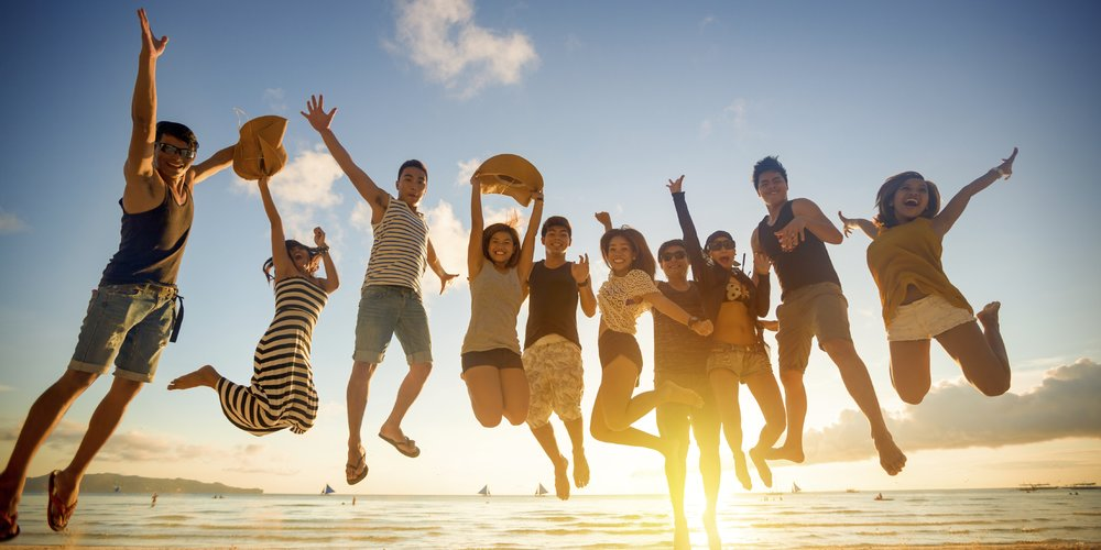 Group of young people jumping on beach