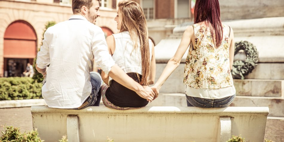 man cheating on her girlfriend at the park. he gives the hand to the girl sitting next to his girlfriend. conceptual image