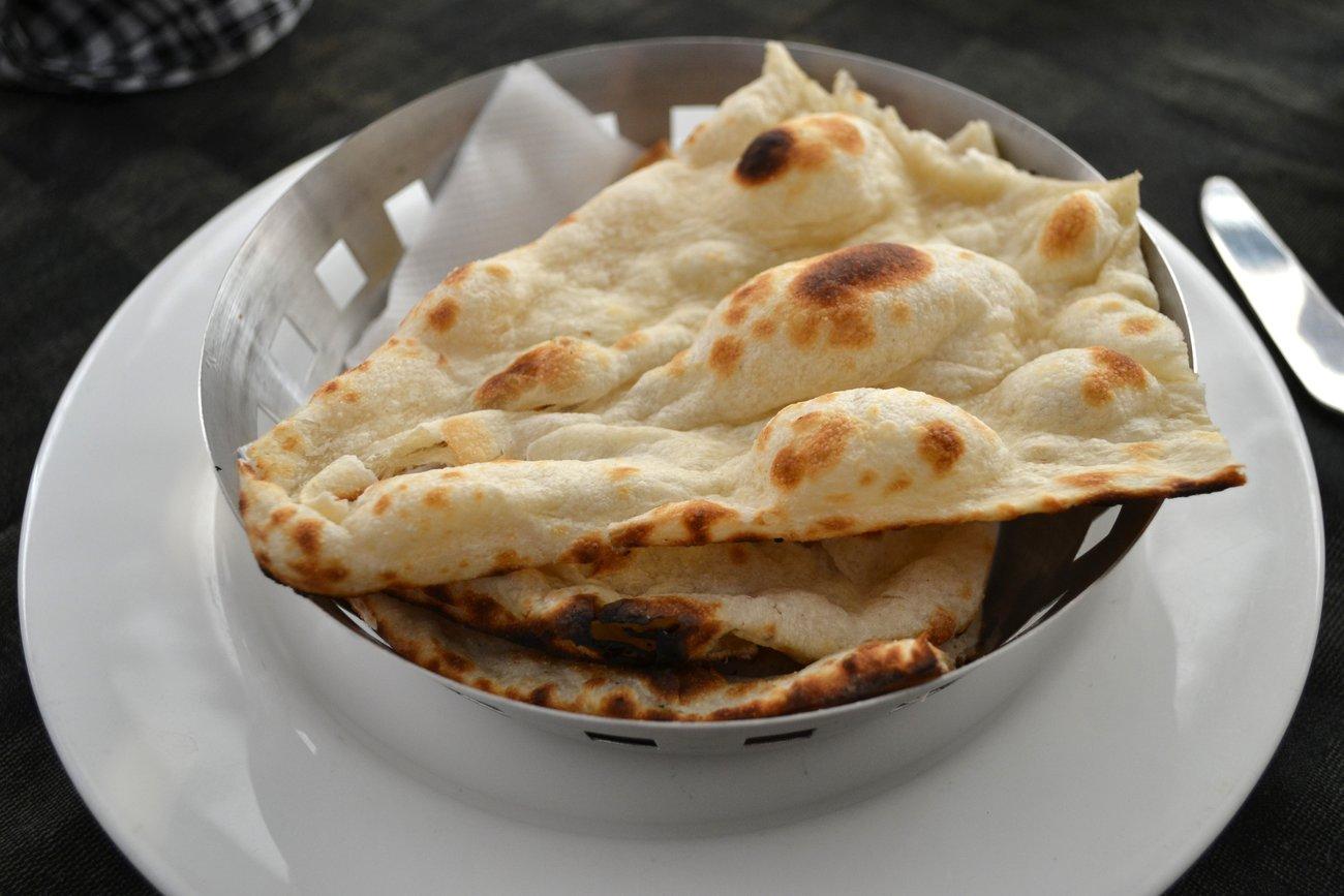 Traditionelles Naan-Brot bekommt durch die Hefe und hohe Hitzezufuhr charakteristische Blasen.