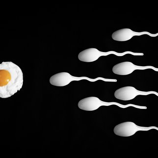 Fried egg and white spoons on black