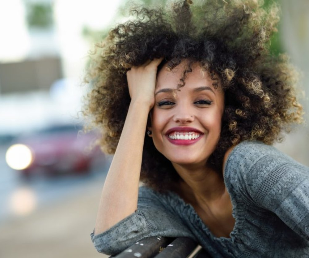 Young mixed woman with afro hairstyle smiling in urban background. Black girl wearing casual clothes.