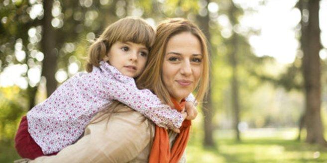 Frau trägt Tochter auf dem Rücken