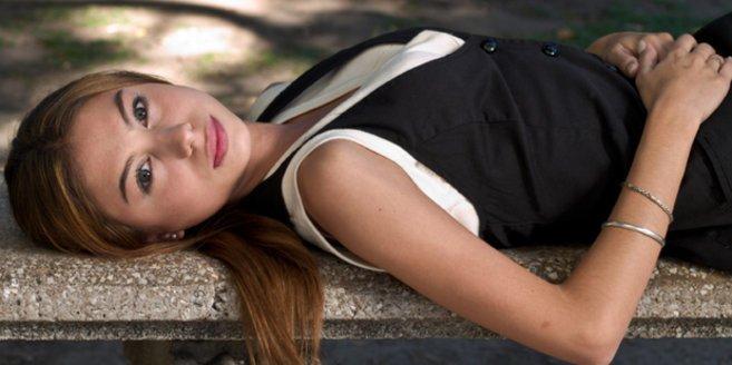 hCG: Junge Frau liegt auf einer Mauer