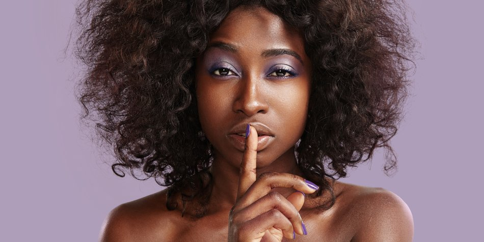 beauty black woman making shhh! on the violet background