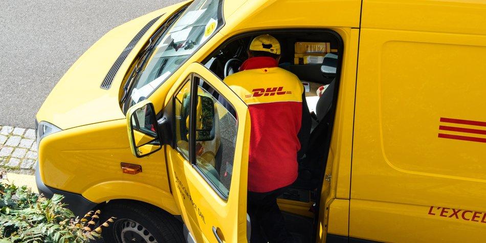Paris, France - April 21, 2016: Courier enters DHL yellow delivery van after delivering the on time delivering package parcel