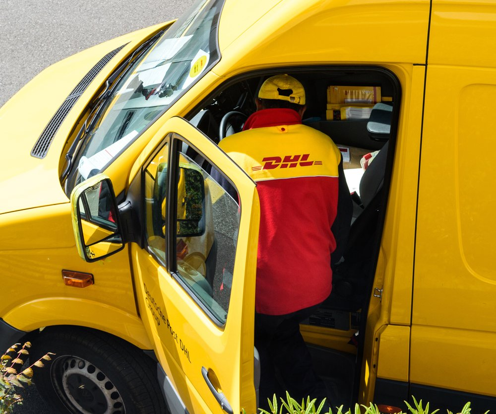 Paris, France - April 21, 2016: Courier enters DHL yellow delivery van after delivering the on time delivering package parcel