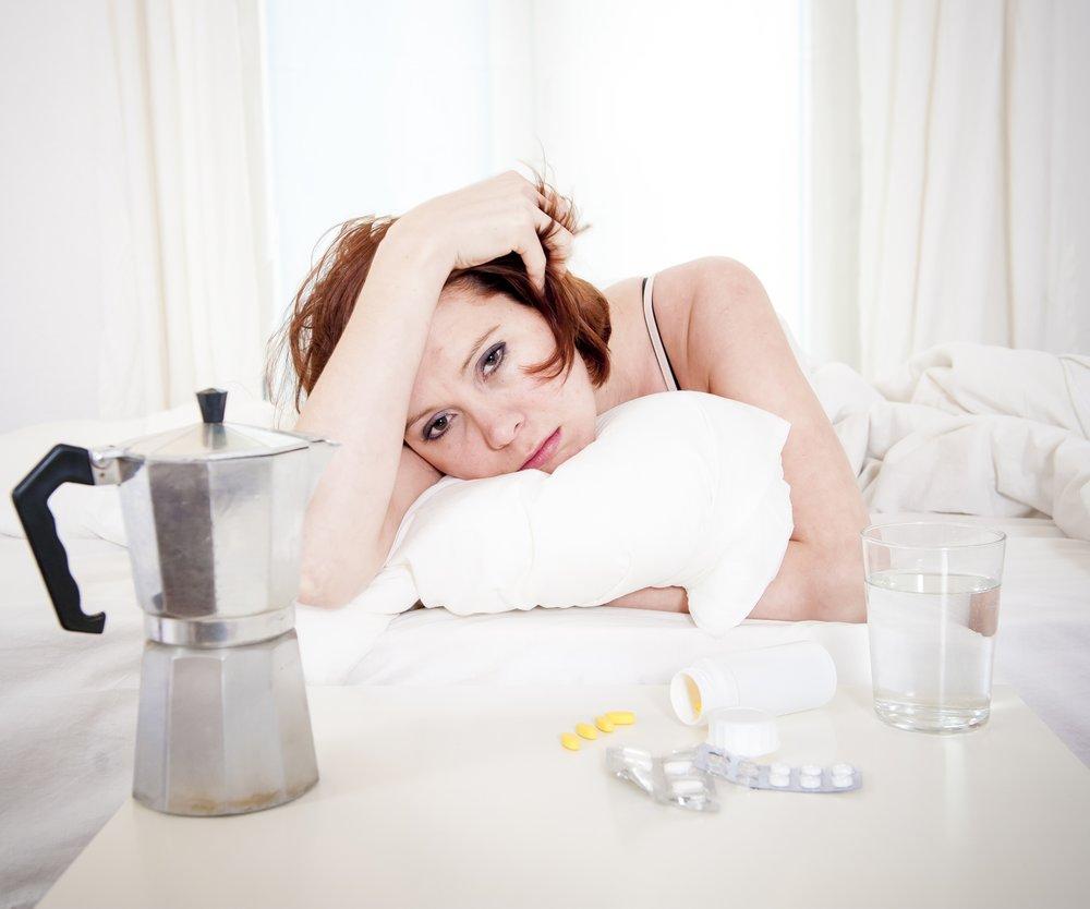 Frau liegt verkatert im Bett