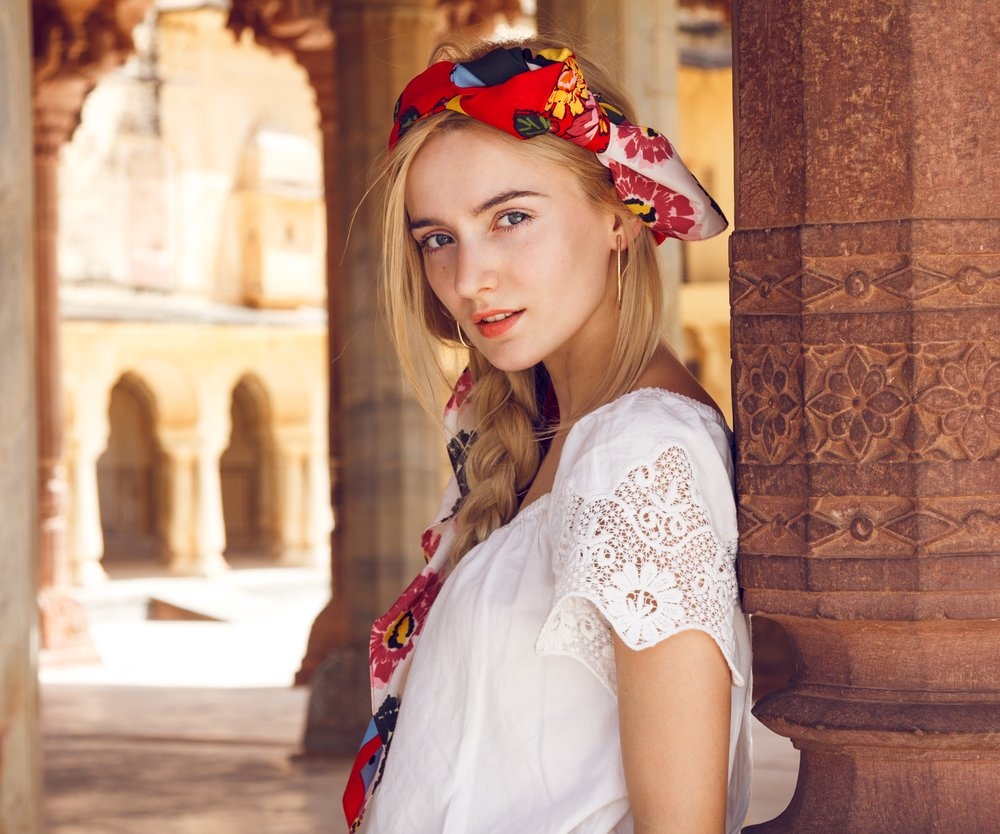 Close-up portrait of a beautiful young woman with a gorgeous scarf on her head. Long blonde hair is tangled in wonderful hairstyle. And she is dressed in a pretty white shirt and captured between old pillars.