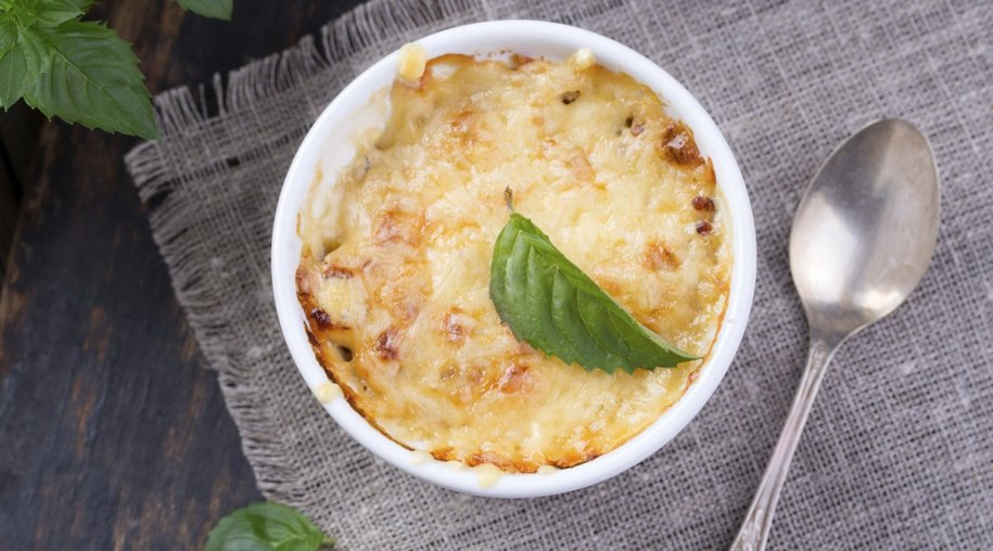 mushroom and potato gratin in white ceramic bowls, on wooden rustic background