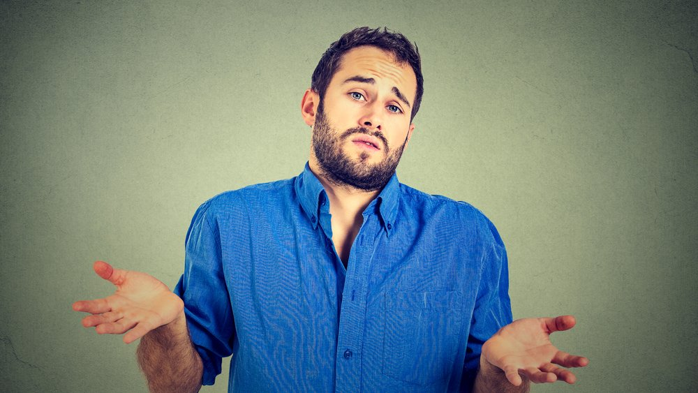 Ignorance and arrogance. Closeup portrait young man shrugging shoulders who cares so what I don't know gesture isolated on gray wall background. Human body language. Whatever attitude reaction .