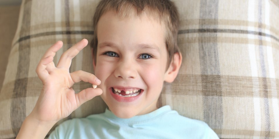 Boy shows gesture OK rejoicing lost baby tooth