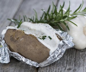 Homemade Baked Potatoe with fresh Herbs on wooden background
