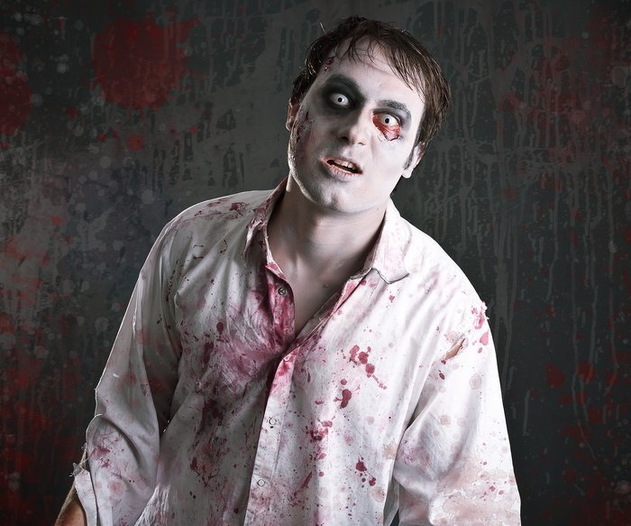 scary zombie with blood splattered white shirt looking into the camera like a zombie does.