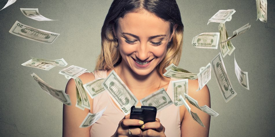 Technology online banking money transfer, e-commerce concept. Happy young woman using smartphone with dollar bills flying away from screen isolated on gray wall office background.