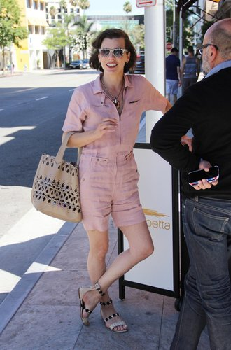 Milla Jovovich in einem rosafarbenen Playsuit