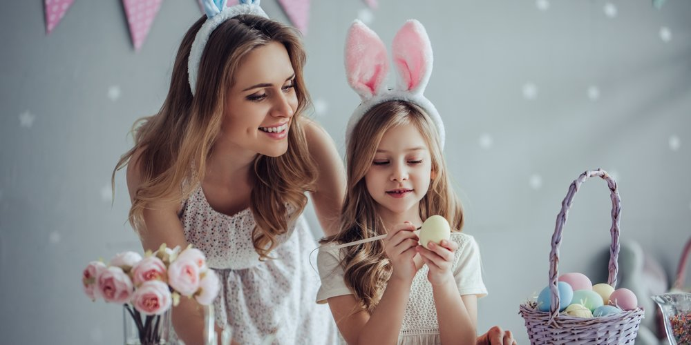 Attractive young woman with little cute girl are preparing for Easter celebration. Mom and daughter wearing bunny ears are spending time together before Easter while painting eggs.