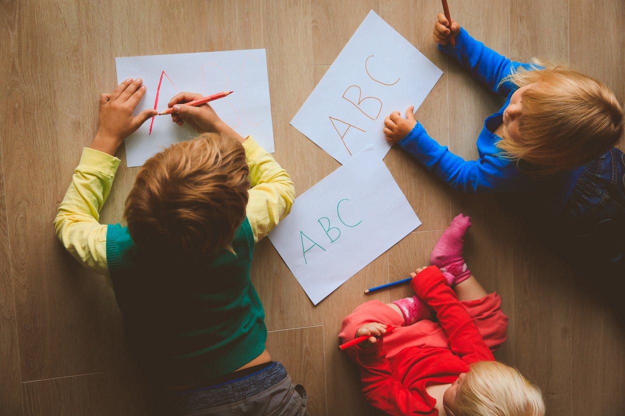 Kinder malen auf Papier auf dem Boden
