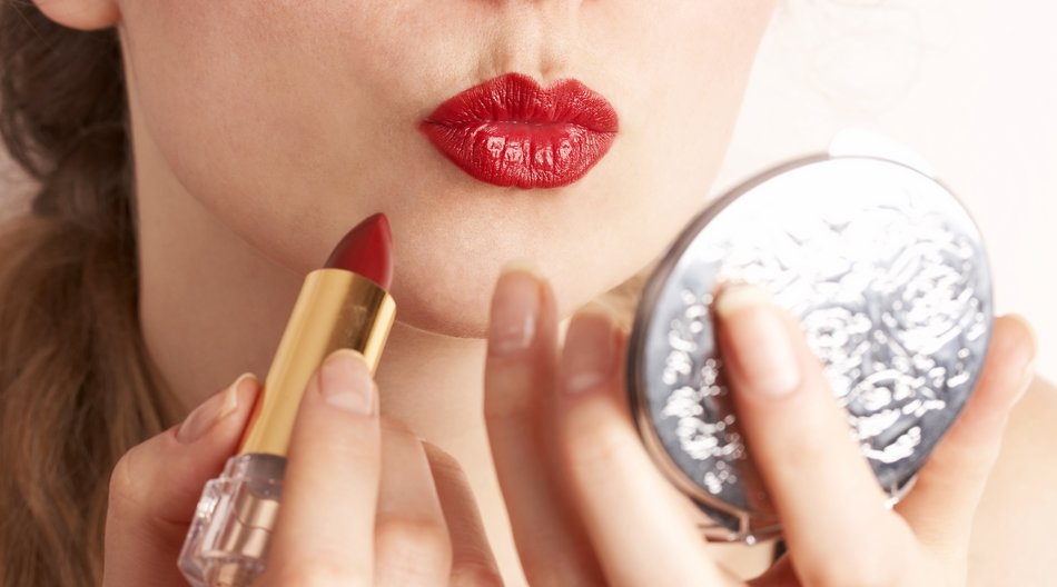 woman applying red lipstick looking in the mirror