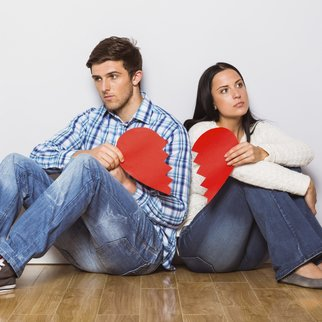 Young couple sitting on floor with broken heart at home