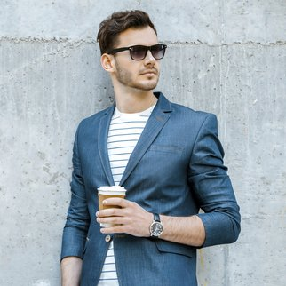 Portrait of stylish handsome young man with bristle standing outdoors and leaning on wall. Man wearing jacket, sunglasses, shirt and holding cup of coffee