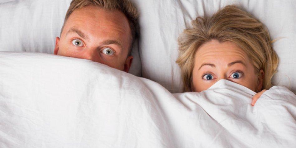 Couple hiding under sheets