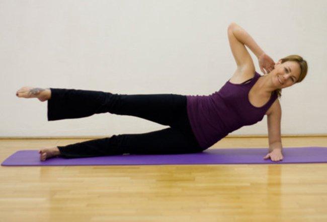 Schritt 1 der Pilatesübung Side Kick Circle, bei der die Pilateslehrerin auf der Seite liegtliegt