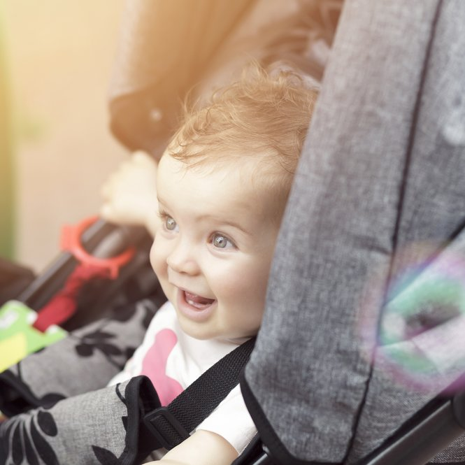Laughing happy baby sitting in a stroller
