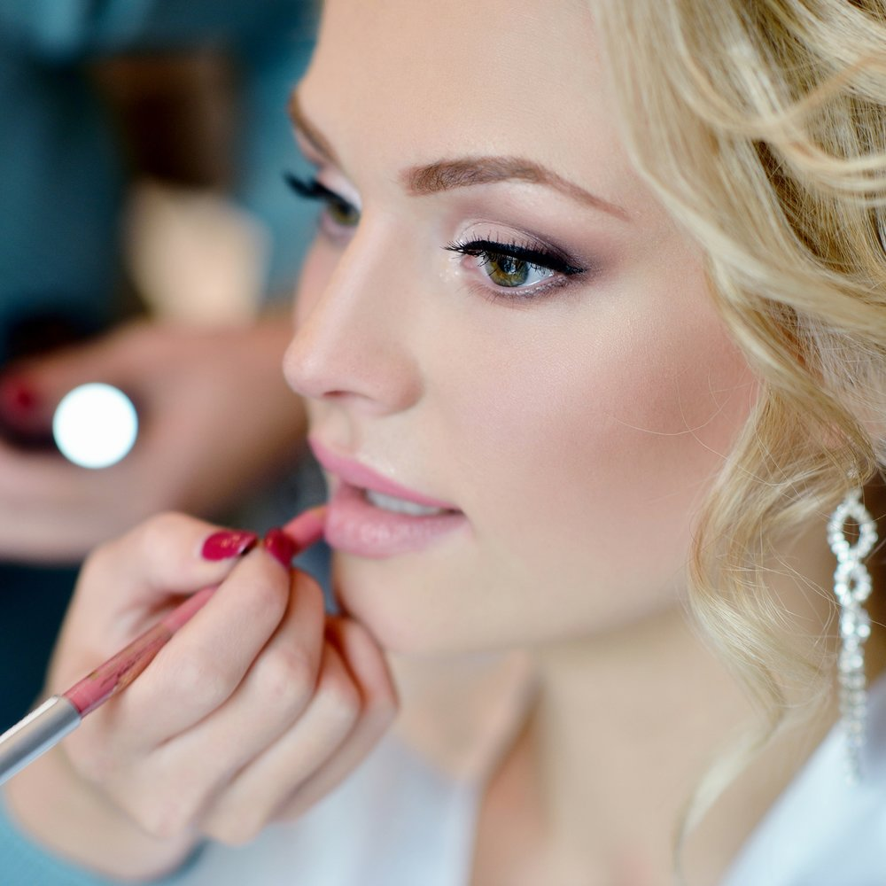 Wedding makeup artist making a make up for bride. Beautiful sexy model girl indoors. Beauty woman with curly hair. Female portrait. Bridal morning of a cute lady. Close-up hands near face