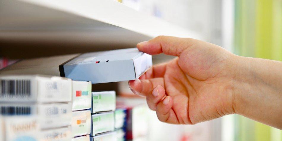 Closeup pharmacist hand holding medicine box in pharmacy drugstore.
