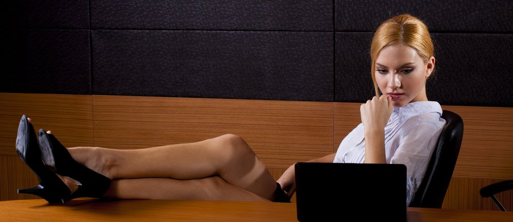 Business Woman with legs on the table in luxry wooden office looking at laptop.