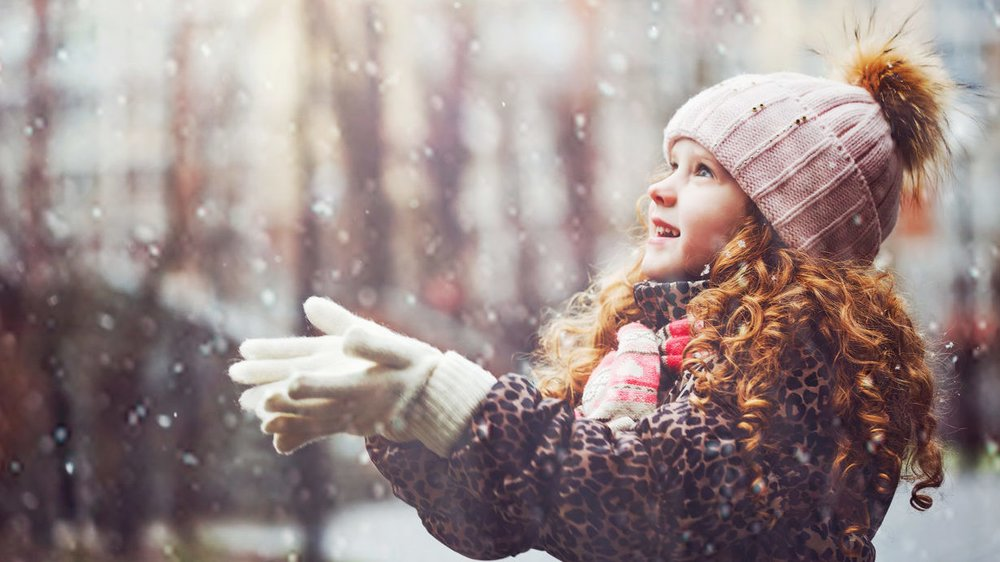 Cute little girl stretches her hand to catch falling snowflakes. First snow.