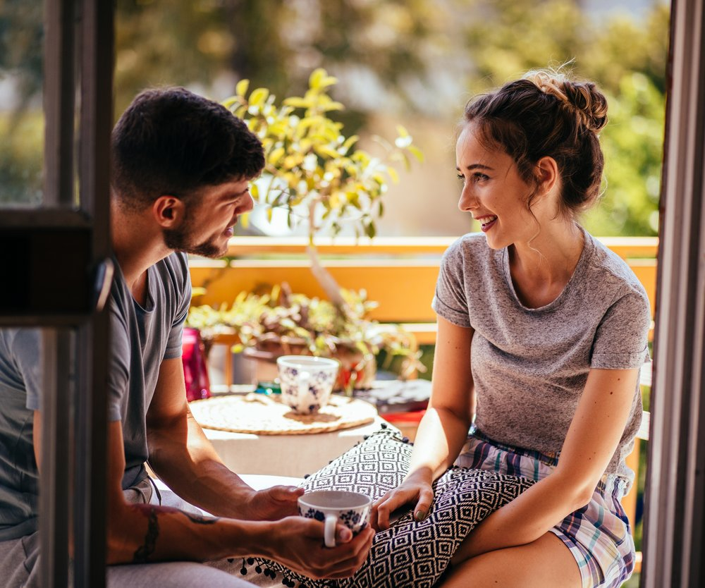 Young hipster couple drinking coffee and talking while sitting on apartment balcony in the morning