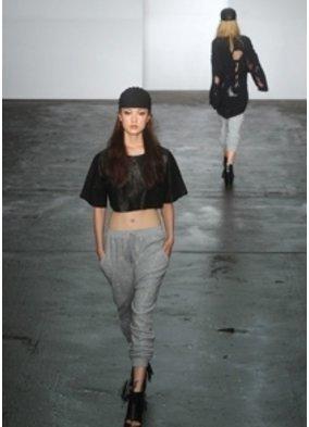 Model auf einem Laufsteg zeigt ein schwarzes bauchfreies Top